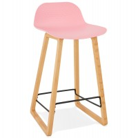 Solid and design pink bar stool with beech legs and metal footrest